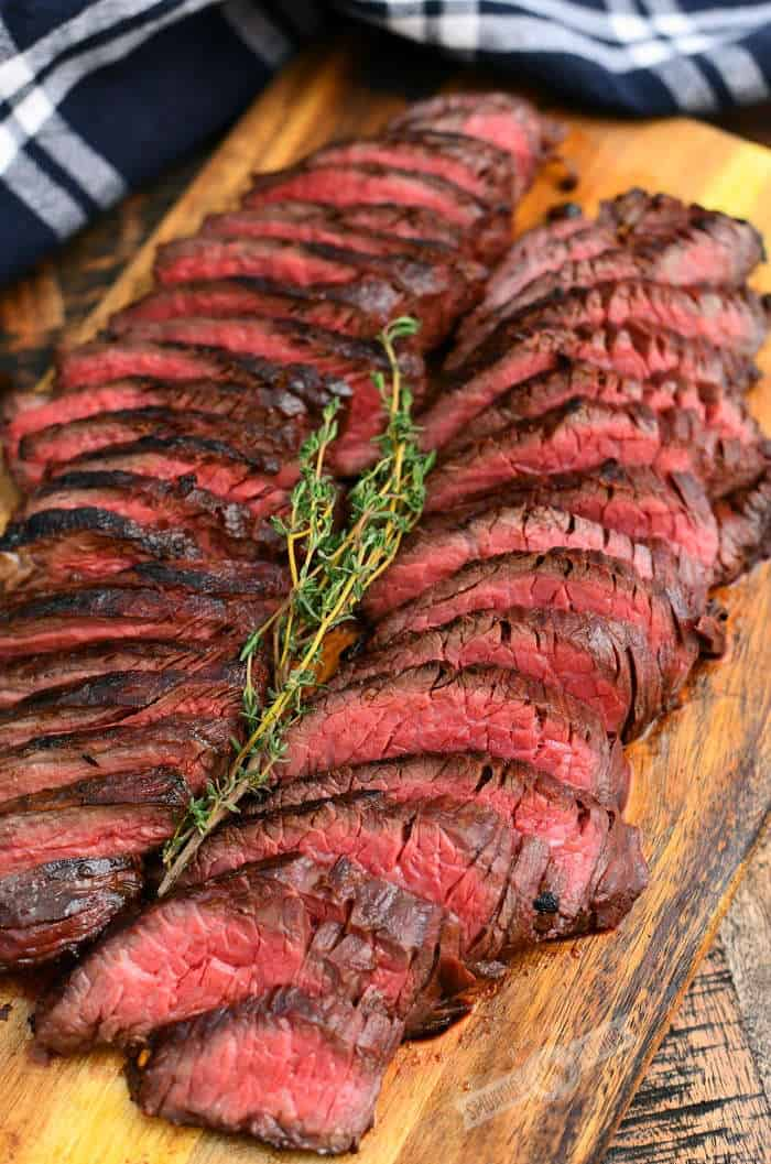 thinly sliced hanger steaks on a cutting board with a sprig of thyme on top