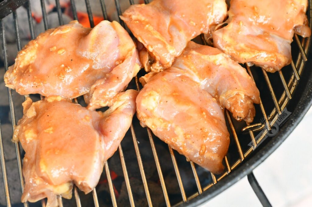 uncooked chicken on the grill with hot charcoal inderneath
