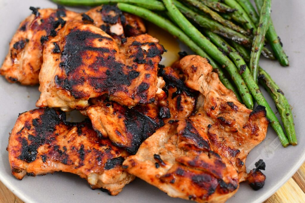 grilled chicken thigs on the grey plate with side of green beans