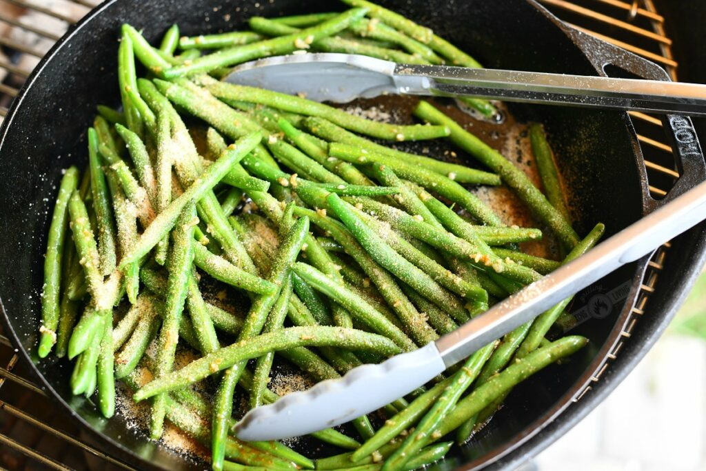 green beans in a skillet topped with seasoning with tongs