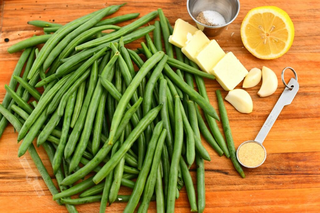 ingredients on a cutting board including green beans, garlic powder, butter, garlic and lemon