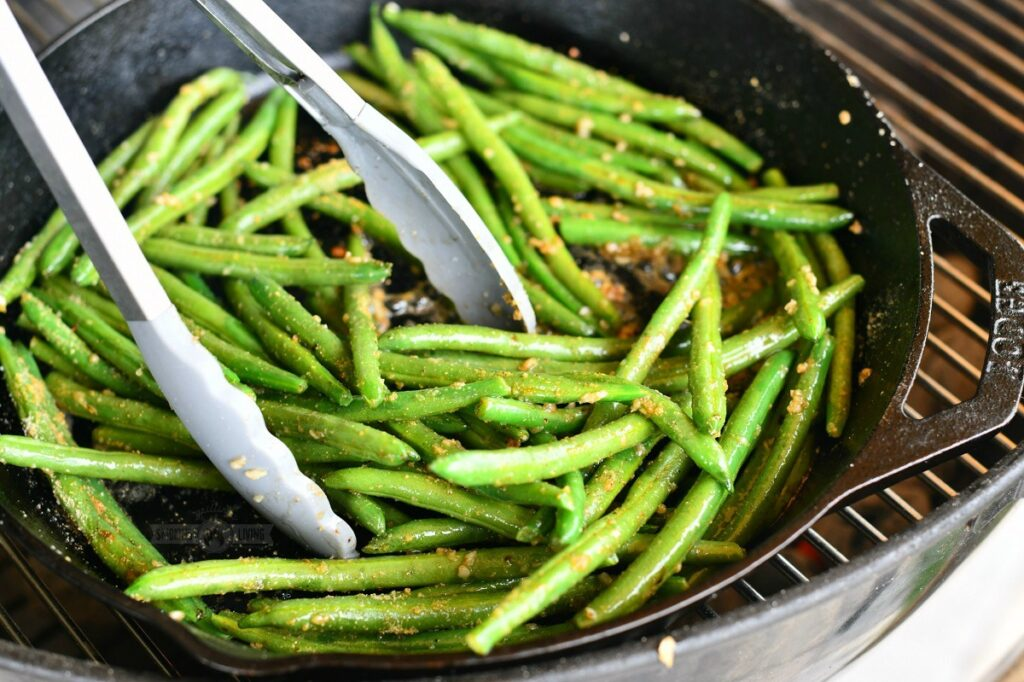 using metal tongs to mix green beans in a skillet