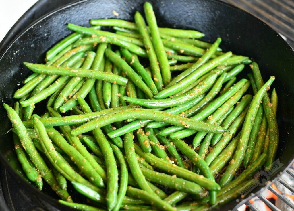 green beans tossed in butter and seasoning in a skillet on the grill