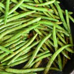 top view of cooked green beans in a skillet on the grill