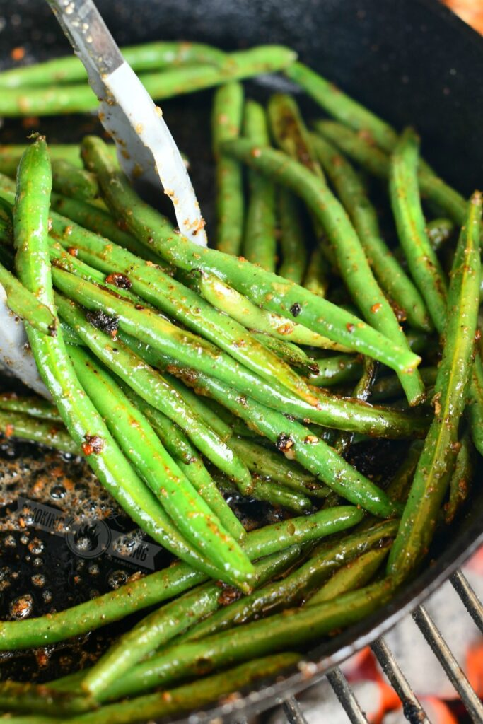 using metal tongs to scoop green beans in a skillet