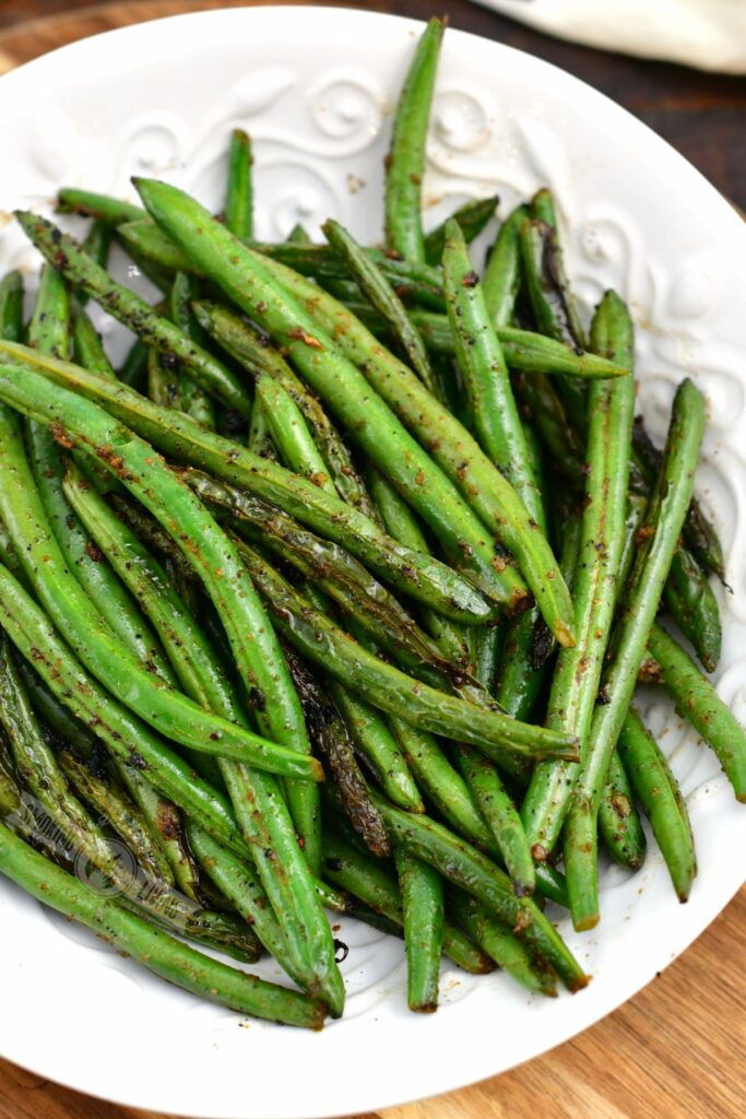 top view of grilled green beans in a white bowl