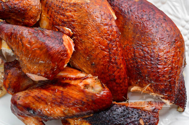 closeup of broken down smoked turkey on a white plate