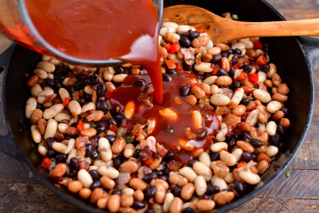 pouring bbq sauce into the skillet with mixed beans and vegetables