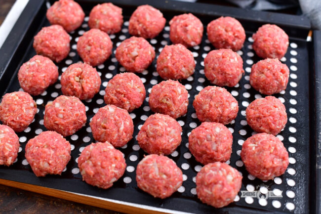 shaped uncooked meatballs on a black metal grate