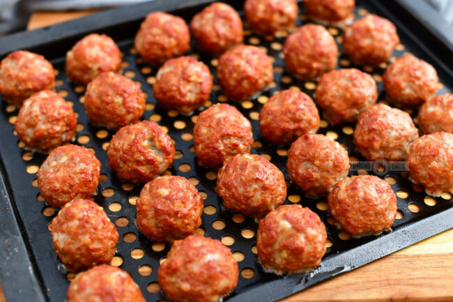 smoked meatballs on a black metal grate