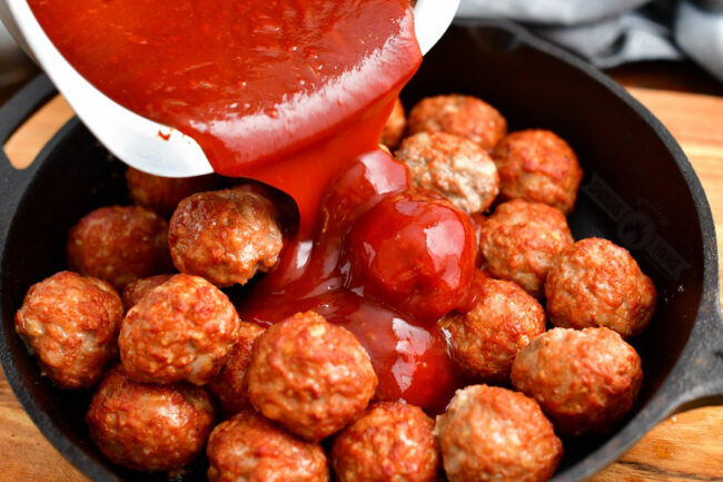 pouring bbq sauce over the meatballs in a skillet