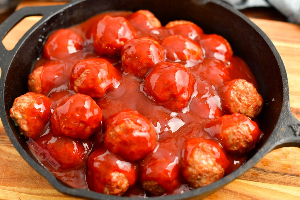 meatballs in a skillet with bbq sauce over them