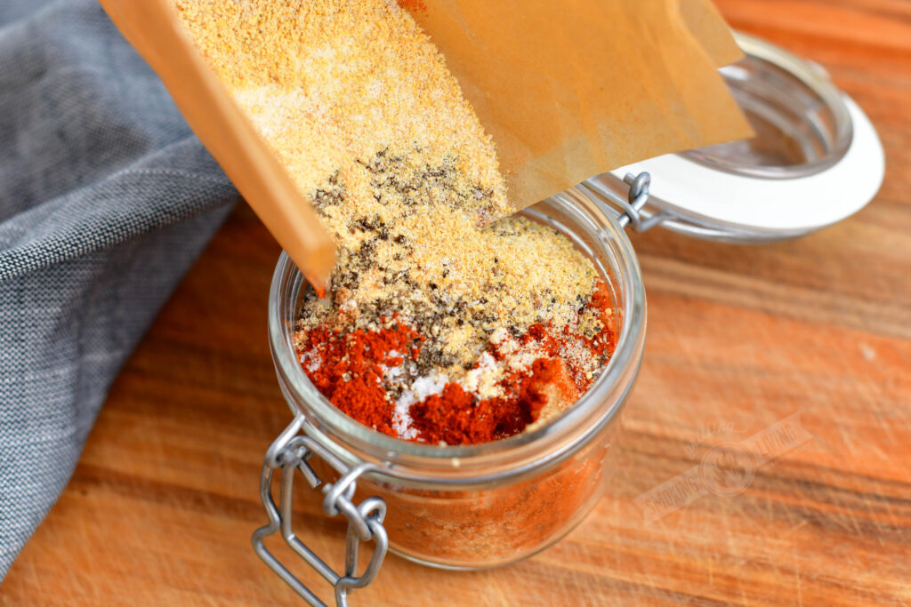 pouring the spice blend into a glass jar