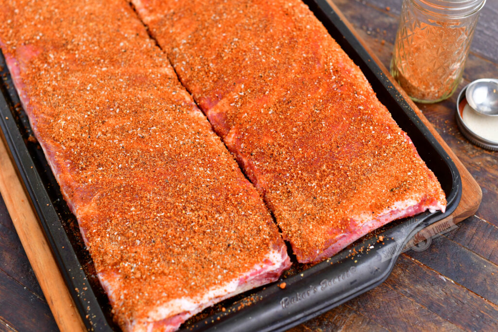 two racks of ribs on a pan rubbed with rib rub