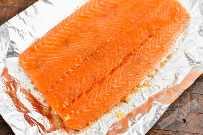 salmon filet on aluminum foil with sugar salt and pepper on top
