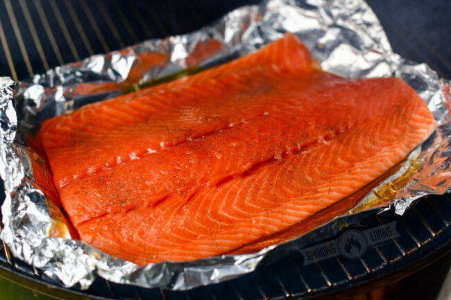 uncooked salmon on sheet of foil on the smoker