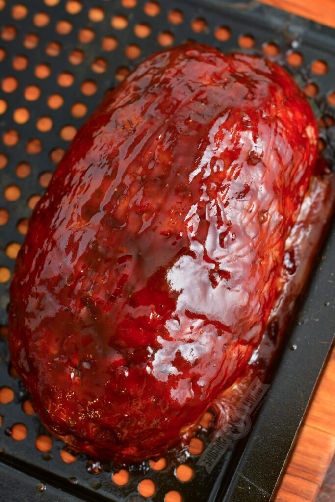 cooked meatloaf on a grill basket brushed with BBQ