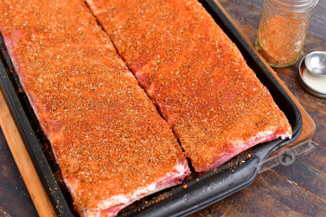 raw St. Louis cur ribs coated in a dry rub in a metal baking sheet