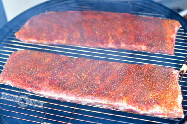 two St. Louis racks of ribs coated in a rub on the smoker