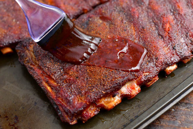 brushing cooked ribs with BBQ sauce