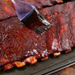 coating cooked St Louis ribs with BBQ sauce using a brush