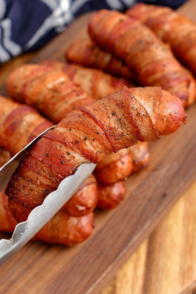 holding smoked sausage with metal tongs