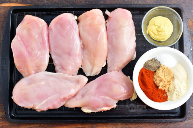 raw chicken breasts, mustard, and seasoning mix on a baking sheet