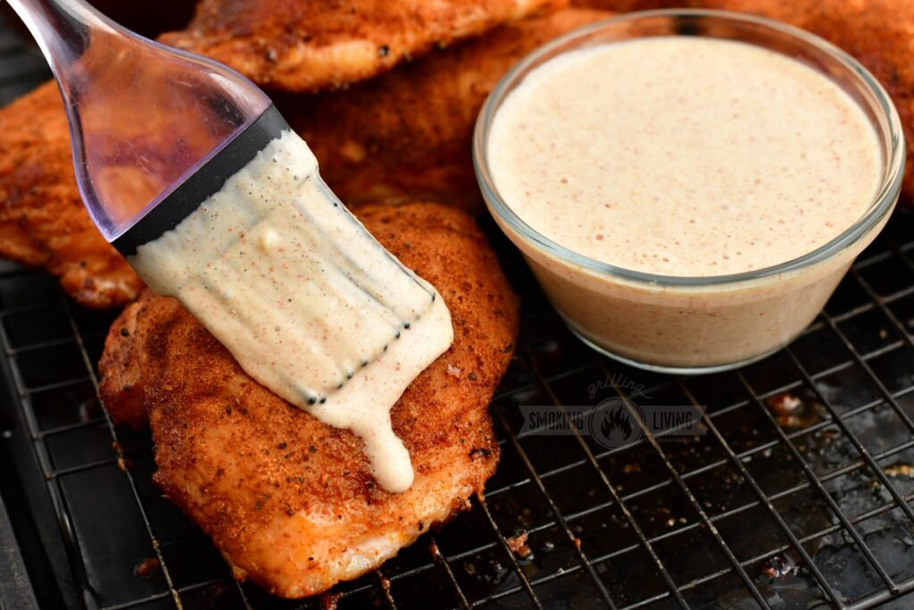 brushing cooked chicken thigh with white BBQ sauce