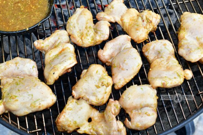 chicken cooking on the grill and marinade in a sauce pan