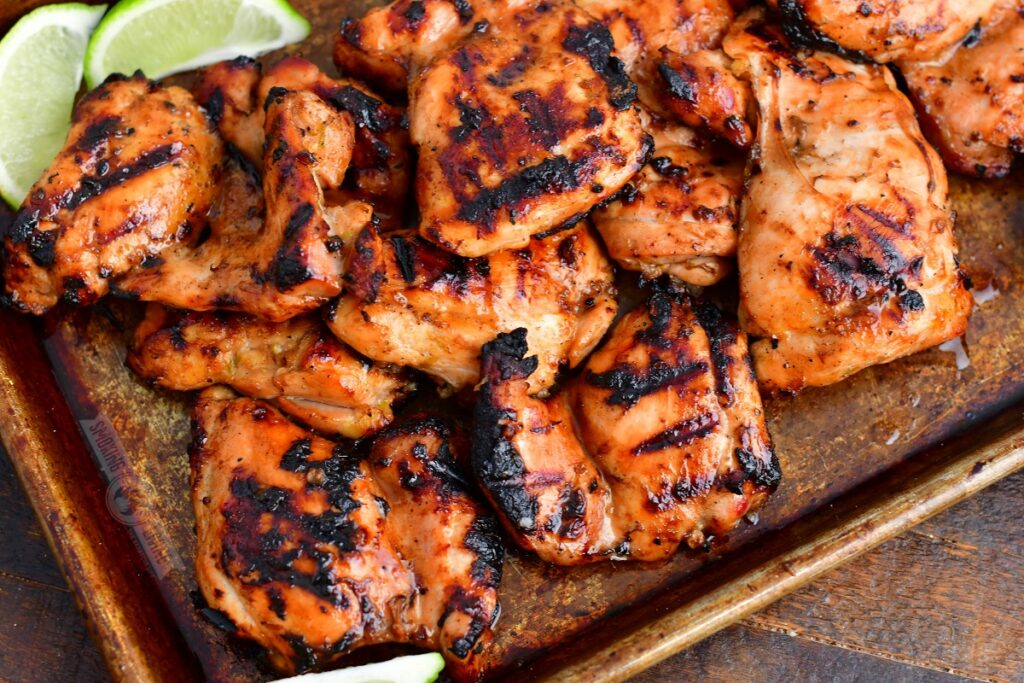 grilled chicken thighs with lime wedges on the metal pan