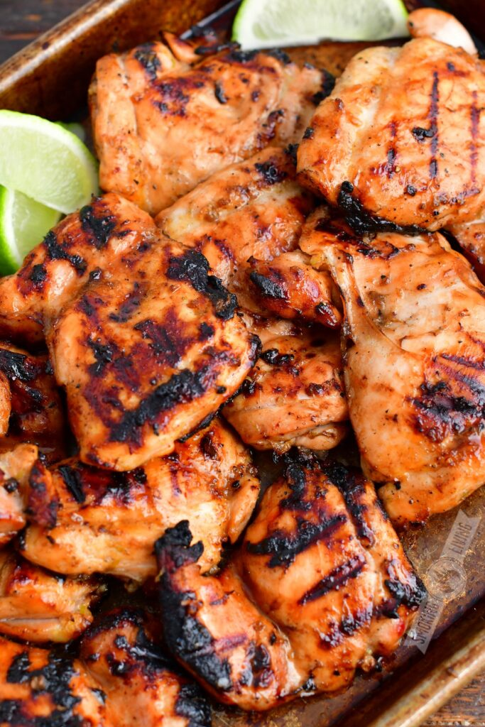 closeup of grilled chicken thighs and lime wedges on a metal pan