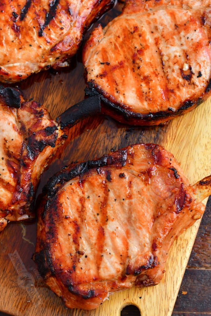 grilled pork chops to view on the wooden plate