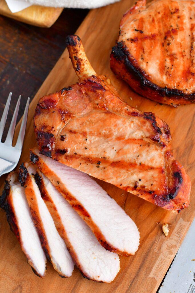 sliced grilled pork chop on a cutting board