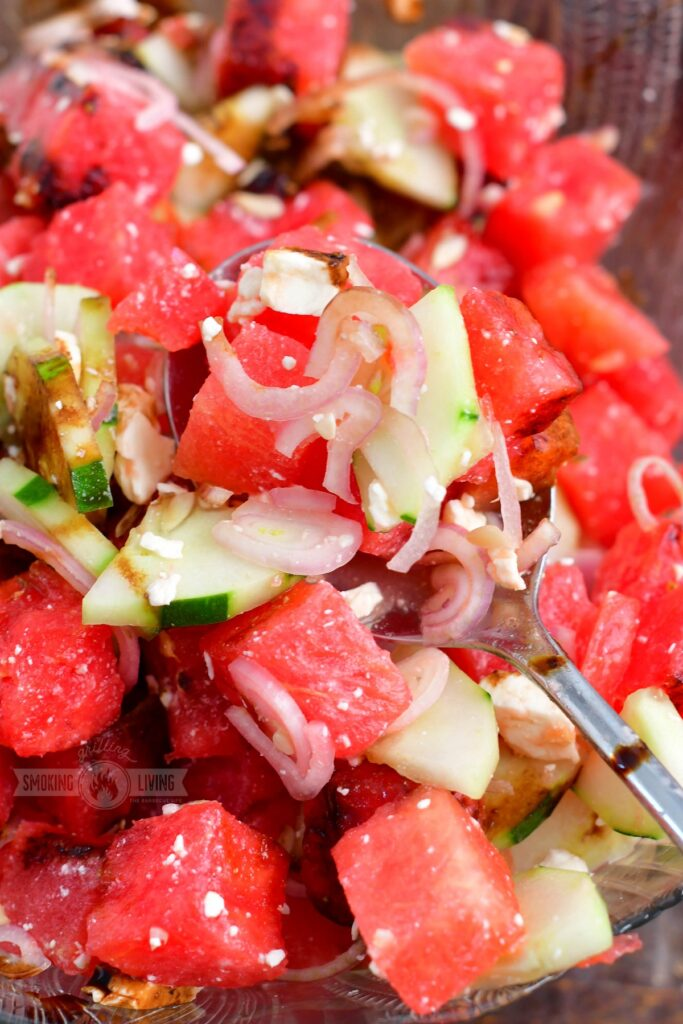spooning watermelon salad with a silver spoon