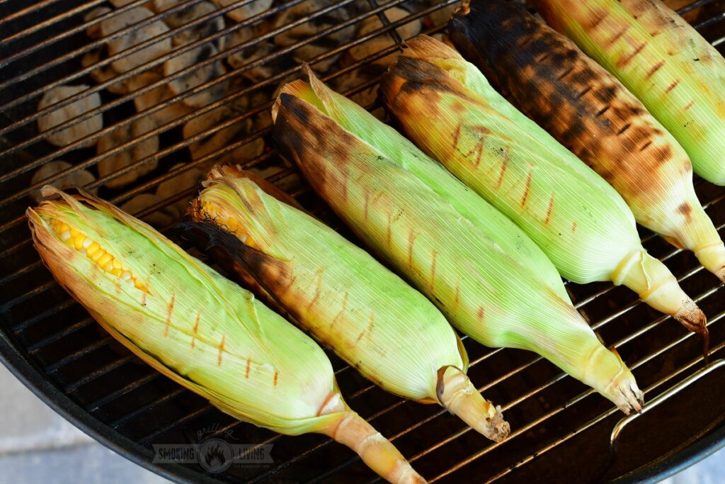 corn in husks grilling on a grill