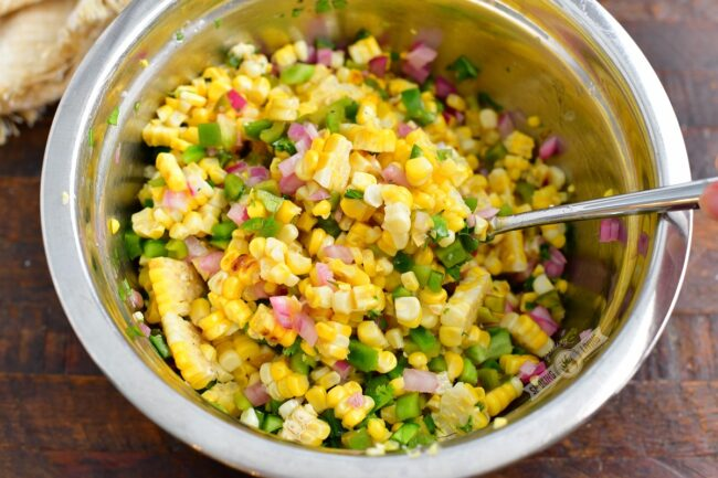 mixing ingredients for the corn salad in a metal bowl