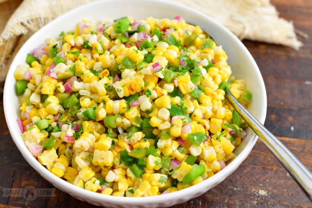 grilled corn salad in a whole serving bowl with a spoon