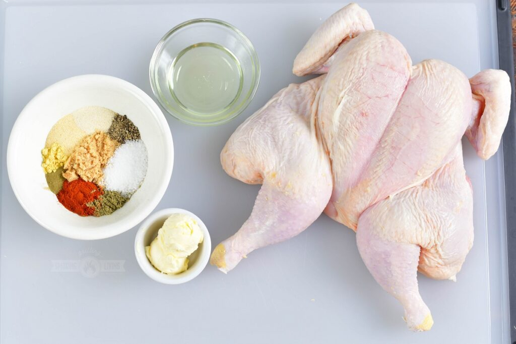 ingredients for smoked spatchcock chicken on white cutting board