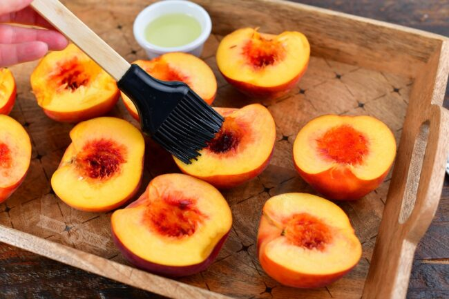 brushing oil with a silicone brush on halves of peaches