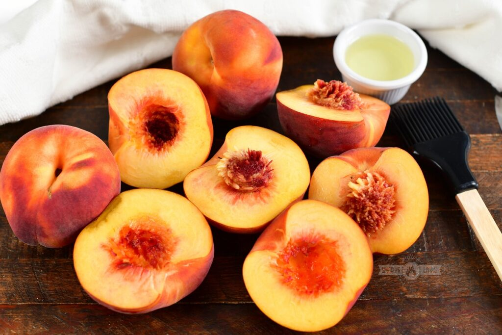 peaches cut in half with a brush and small cup of oil