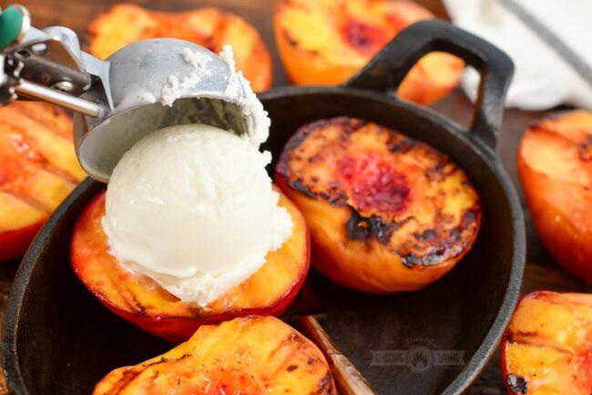 adding scoop of vanilla ice cream of a grilled peach