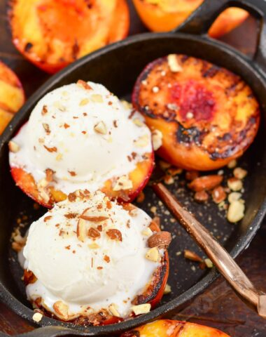 top view of grilled peaches topped with ice cream on a cast iron dish